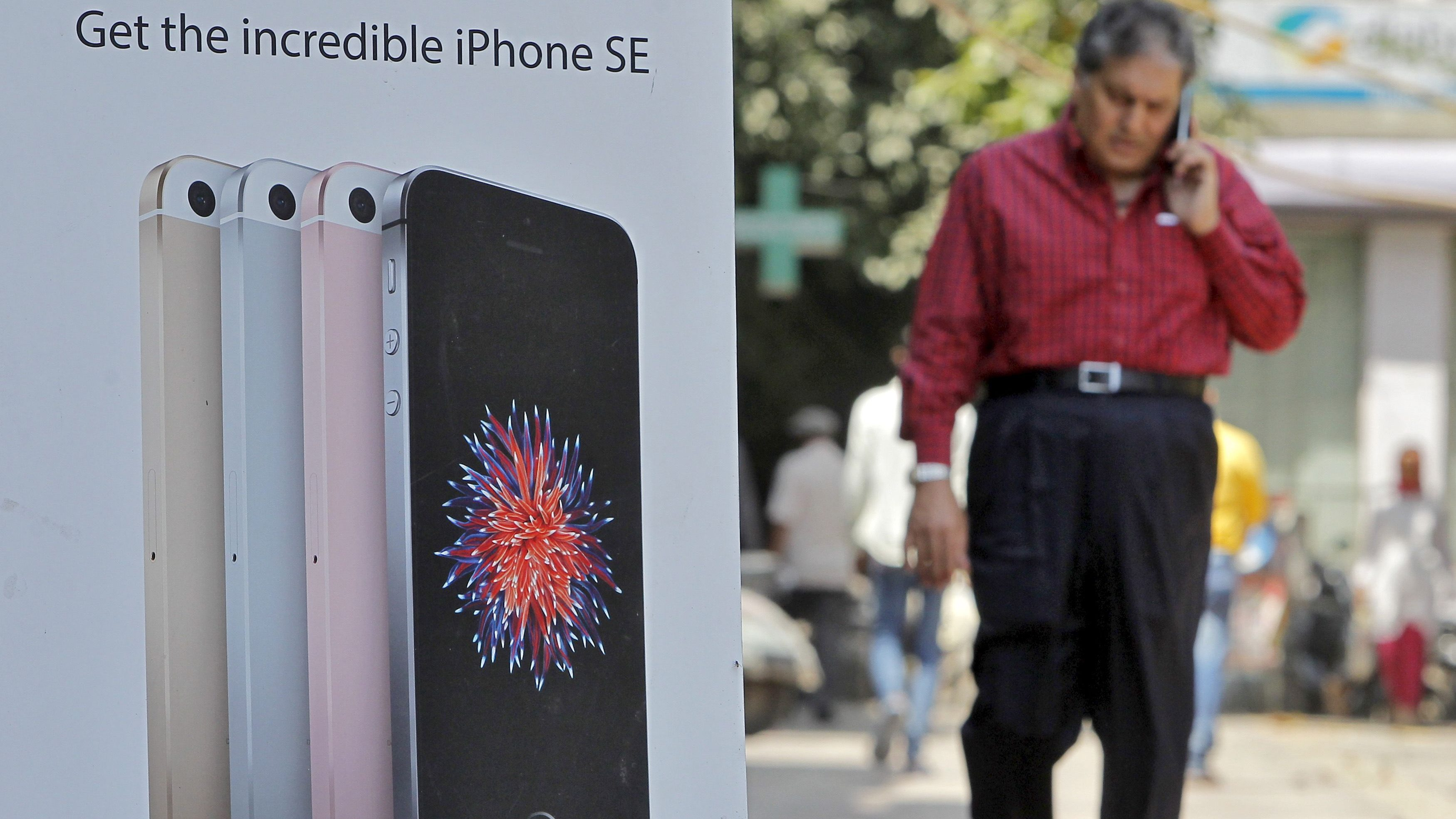 65a46e55f26 A man speaks on his mobile phone as he walks past an Apple iPhone SE  advertisement