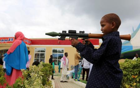 A Somali boy plays with a toy model of a rocket-propelled grenade (RPG) after attending Eid al-Fitr prayers to mark the end of the fasting month of Ramadan in Somalia's capital Mogadishu, July 6, 2016.
