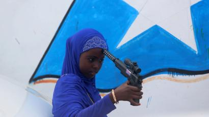 A Somali girl plays with a toy gun after attending Eid al-Fitr prayers to mark the end of the fasting month of Ramadan in Somalia's capital Mogadishu, July 6, 2016.