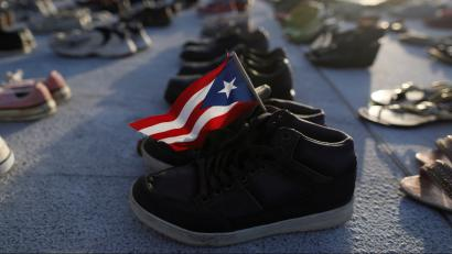 A Puerto Rican flag is seen on a pair of shoes as hundreds of pairs of shoes displayed at the Capitol to pay tribute to Hurricane Maria's victims