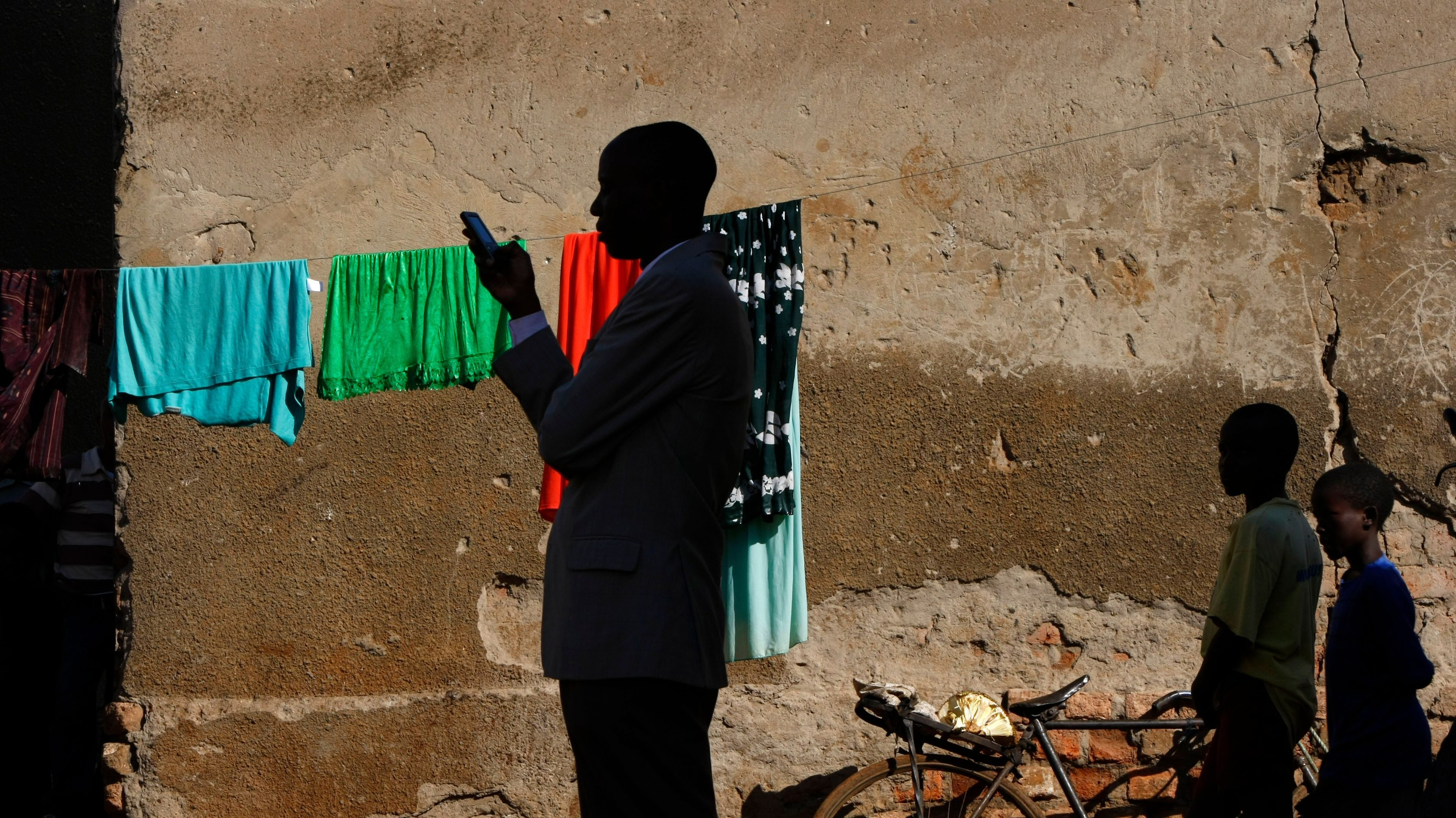 A town official accompanying visiting journalists sends a text message on his phone in the slum of Kachuf in the Masaka district of southern Uganda March 24, 2009. The word 'Kachuf' in Luganda means 'dirt'. MALTA OUT. NO COMMERCIAL OR EDITORIAL SALES IN MALTA