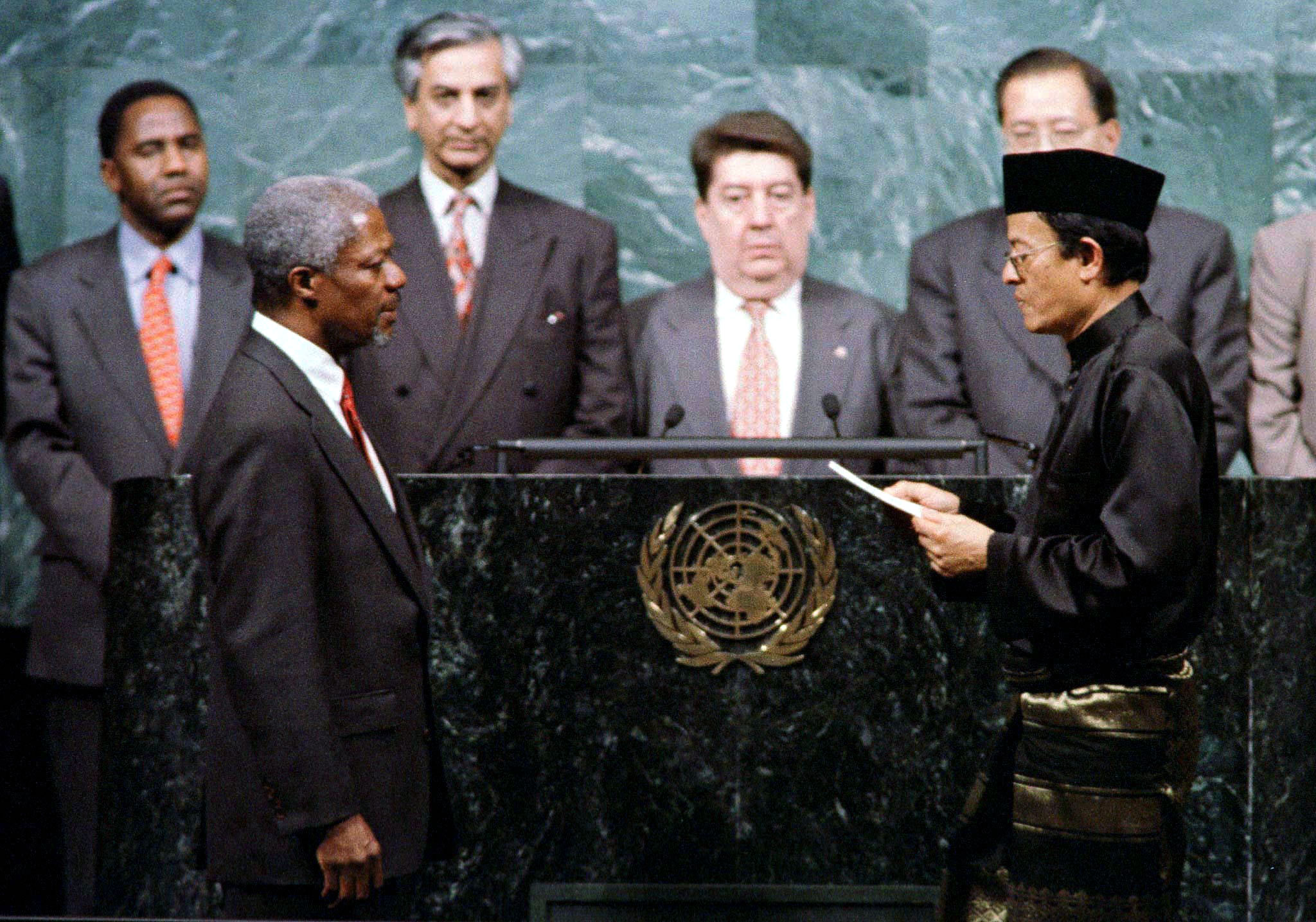 Kofi Annan of Ghana (front L) takes the oath of office as the new United Nations Secretary General from U.N. General Assembly President Razali Ismail of Malaysia (front R) at U.N. headquarters December 17. Kofi Annan is to succeed outgoing Secretary General-Boutros-Boutros-Ghali of Egypt whose term expires December 31. People at rear are unidentified. - PBEAHUMYSDY