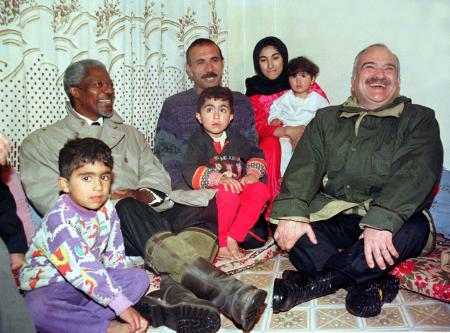 United Nations Secretary General Kofi Annan (L) and Jordan's Crown Prince Hassan (R ) meet with a Palestinian family during their tour at Hitteen Palestinian refugee camp near Amman March 18. Annan on the first leg of a nine-day tour of the Middle East is expected to discuss latest regional developments with its leaders.