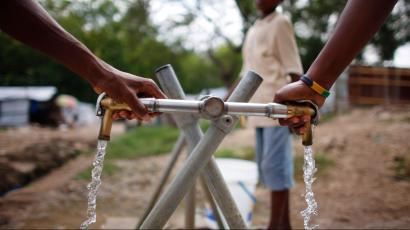 Two hands on a water pump.