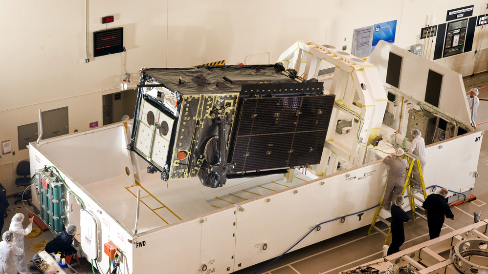 A satellite roughly the same size as Space Vehicle Four is loaded into a transport container.