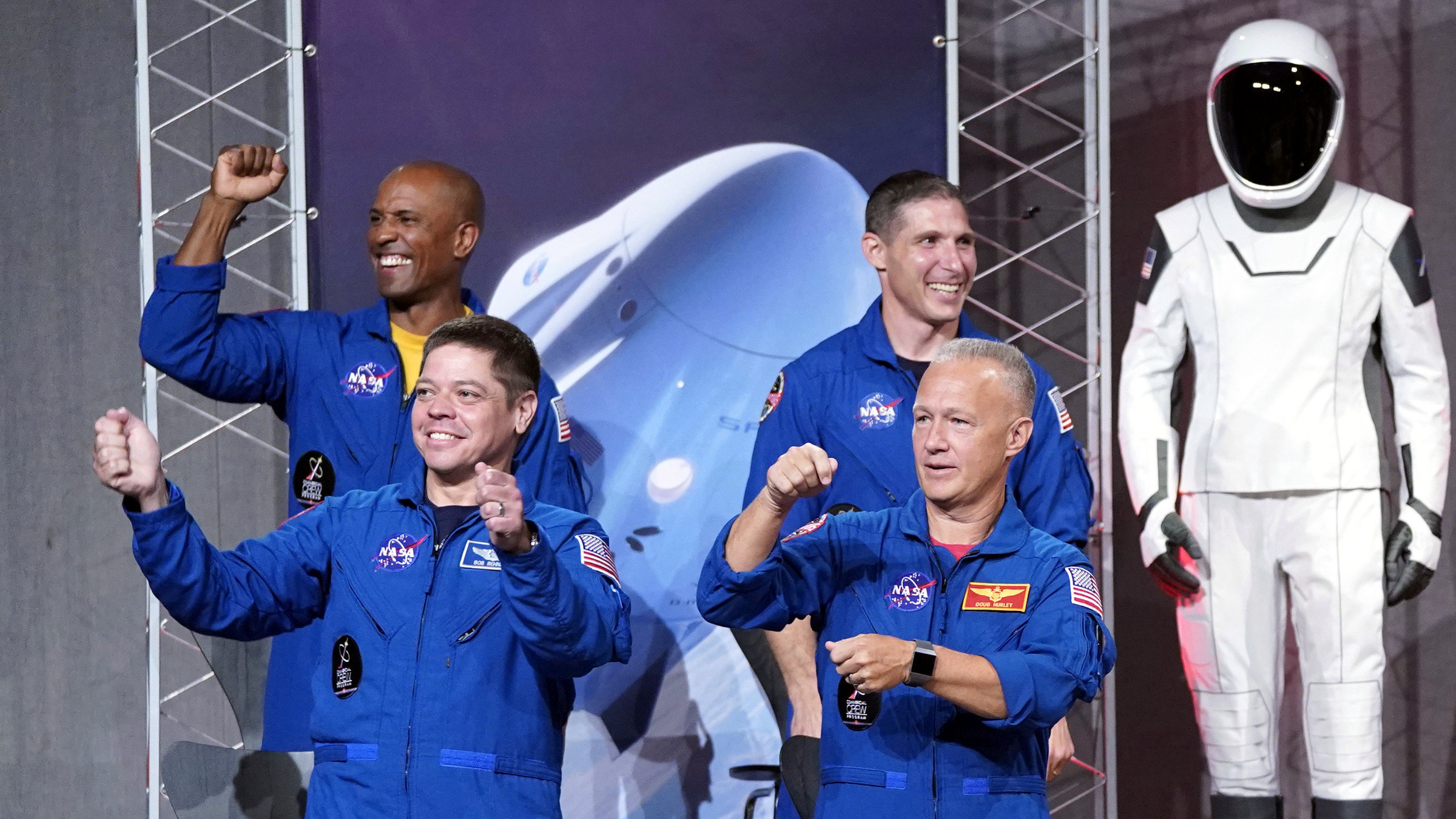 Astronauts, from left to right, Victor Glover, Robert Behnken, Michael Hopkins and Douglas Hurley, acknowledge the crowd after being introduced at a NASA event to announce them as astronauts assigned to crew the first flight tests and missions of the Boeing CST-100 Starliner and SpaceX Crew Dragon, Friday, Aug. 3, 2018, in Houston. The astronauts will ride the first commercial capsules into orbit next year and return human launches to the U.S.