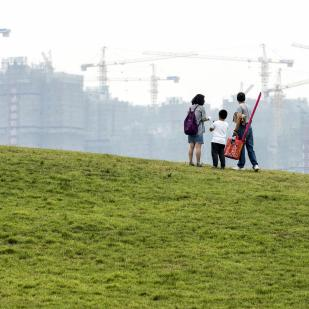 A family stands on an artificial grassland near a construction site of a residential complex, in Hefei, Anhui province, China.