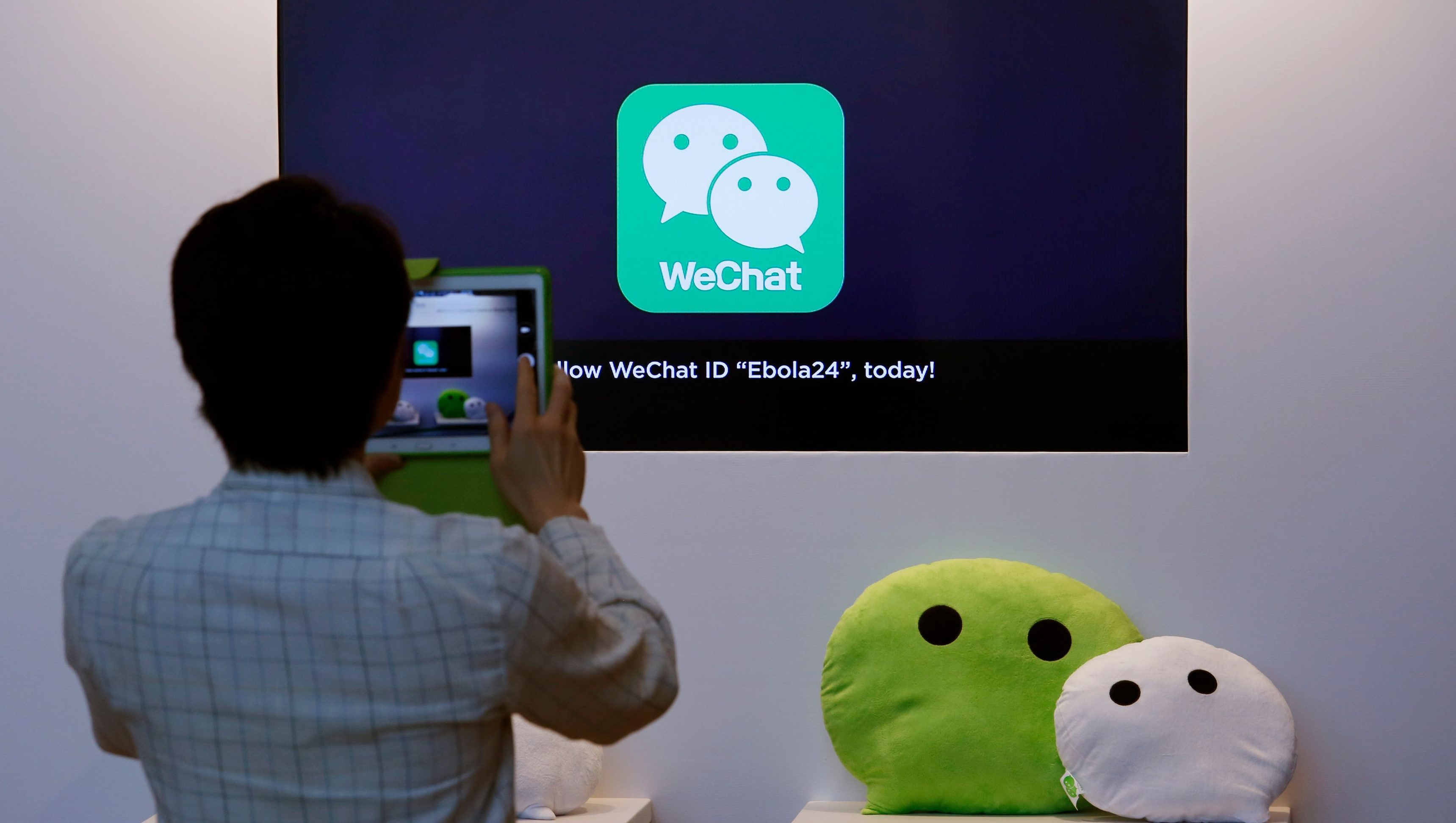 A man takes a photograph of a counter promoting WeChat, a product of Tencent, displayed at a news conference announcing the company's results in Hong Kong March 18, 2015. Tencent Holdings Ltd , China's biggest social network and online entertainment firm, posted a 51 percent gain in fourth-quarter net income, missing estimates, as sharing and content costs took a bite out of healthy revenue growth. REUTERS/Bobby Yip (CHINA - Tags: BUSINESS SCIENCE TECHNOLOGY HEALTH) - GM1EB3I1G4401