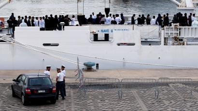 """Migrants waits to disembark from Italian coast guard vessel """"Diciotti"""" as they arrive at the port of Catania, Italy, August 21, 2018."""