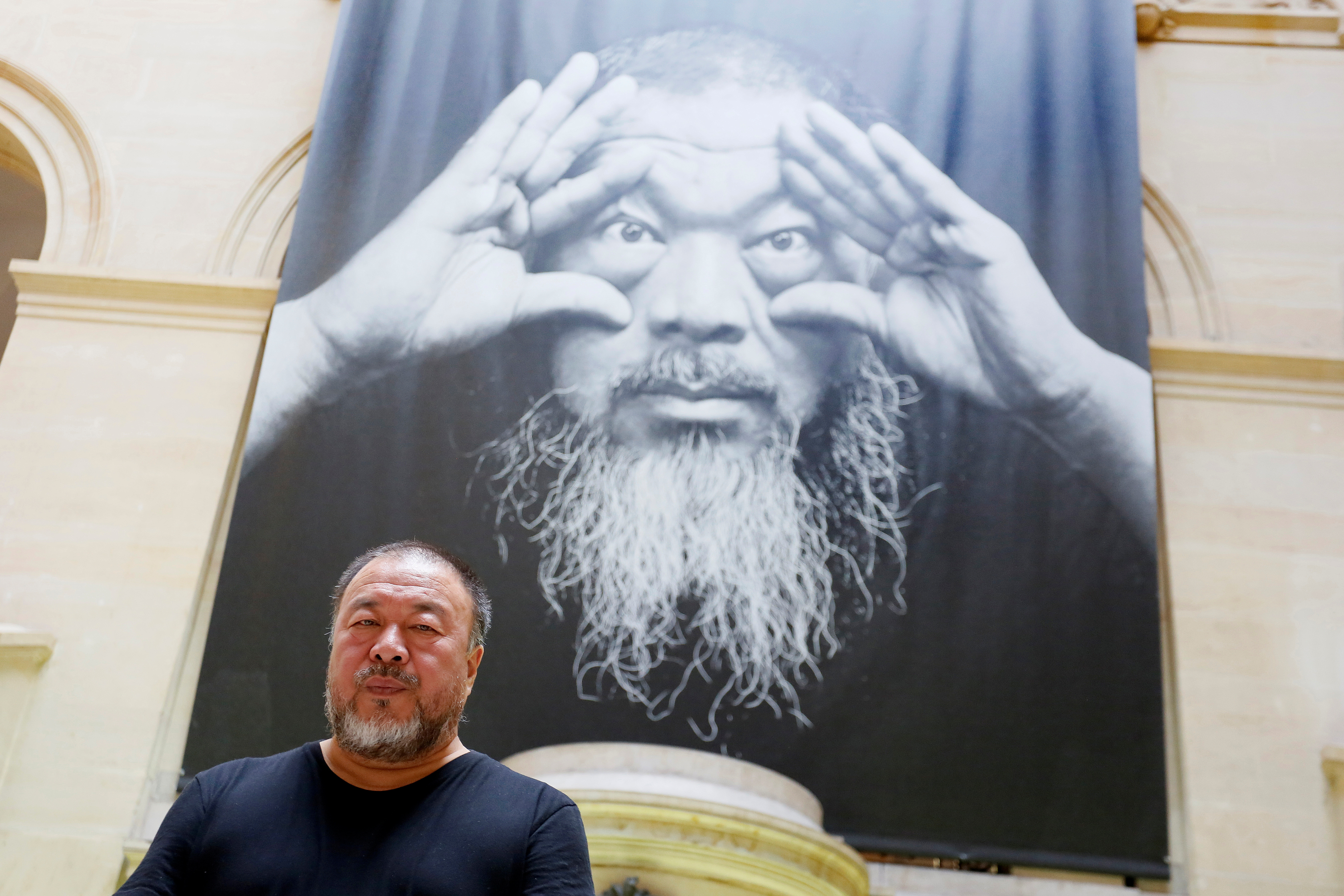 "Ai Weiwei poses under the poster of an exhibition titled ""Ai Weiwei: By the way, it's always the others"" in Switzerland."