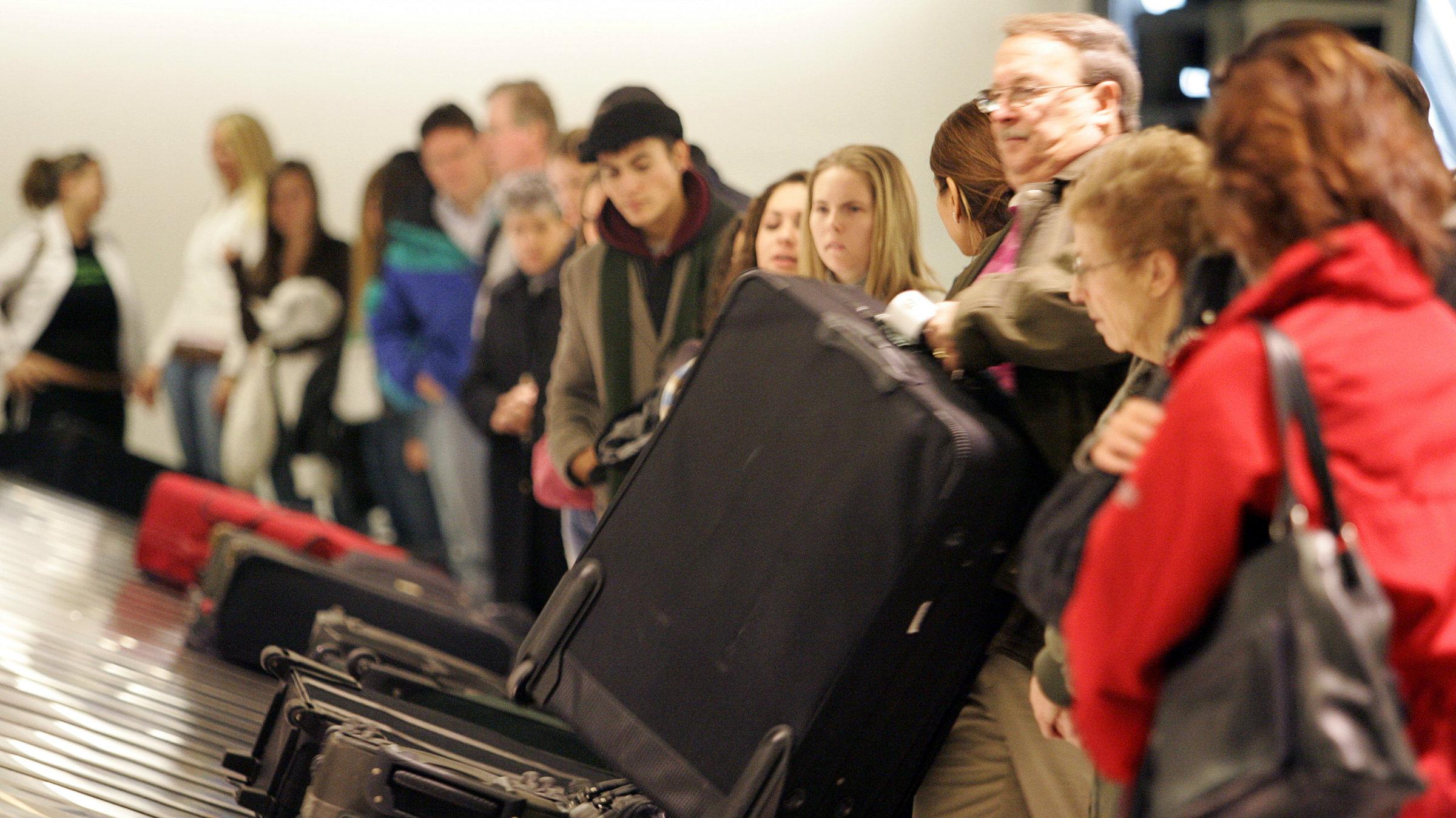 Travelers claim their baggage at Newark Liberty International Airport