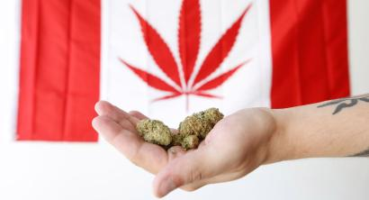 An employee holds marijuana in front of a modified Canadian flag with a marijuana leaf while posing in a photo illustration at a dispensary in Ottawa, Ontario, Canada, June 20, 2018.
