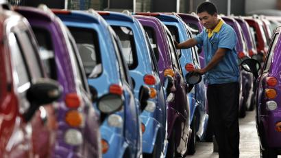 An employee checks newly-assembled electric cars to be exported to South America at an electric vehicle factory in Zouping county, Shandong province September 24, 2013. Growth in China's factory sector accelerated to a six-month high in September, a preliminary survey showed on Monday, as stronger domestic and foreign demand added to recent signs of a tentative turnaround in the world's second-largest economy. Picture taken September 24, 2013. REUTERS/China Daily (CHINA - Tags: BUSINESS TRANSPORT) CHINA OUT. NO COMMERCIAL OR EDITORIAL SALES IN CHINA