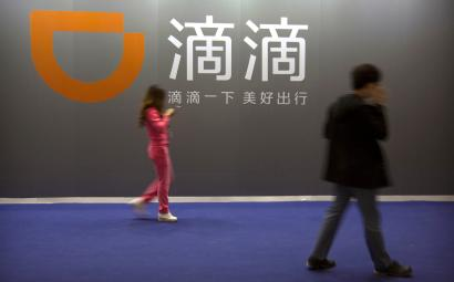 FILE - In this April 27, 2017, file photo, visitors walk past a sign for Chinese ride-hailing service Didi Chuxing at the Global Mobile Internet Conference (GMIC) in Beijing. Chinese mobile service giant Didi Chuxing and Tokyo-based SoftBank Corp. have set up a joint venture for taxi-hailing in Japan. The companies announced the plan Thursday, July 19, 2018, for a service that uses artificial intelligence and data analysis on a technology platform available for free to all taxi companies in Japan. (AP Photo/Mark Schiefelbein, File)