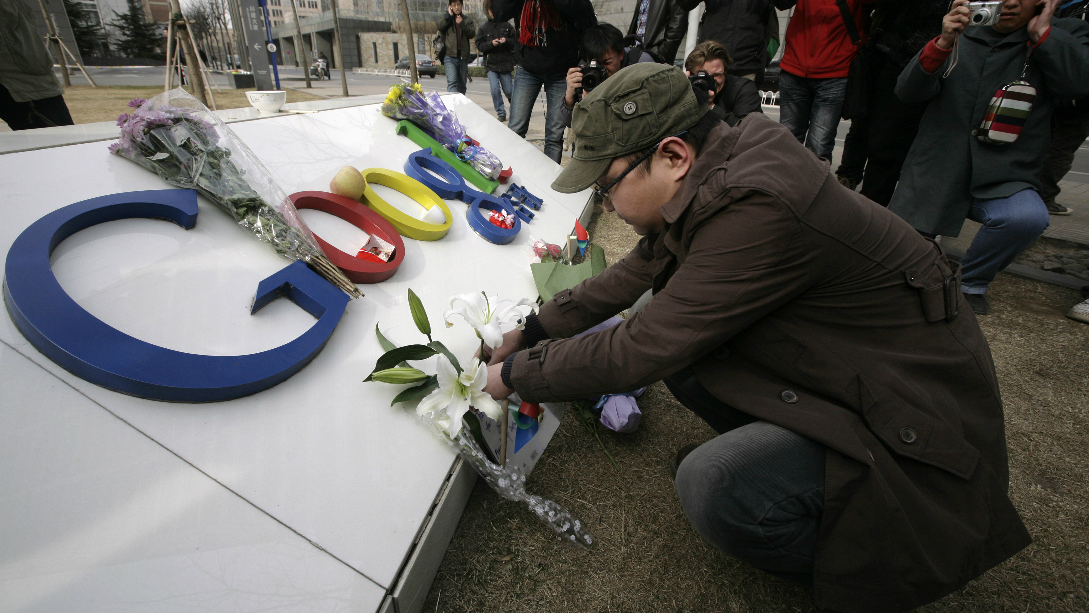 A man places flowers on the Google logo at its China headquarters building in Beijing March 23, 2010. Google Inc shut its mainland Chinese-language portal and began rerouting searches to an uncensored Hong Kong-based site, unleashing a blast of ire from Beijing and prompting concerns over its future business in China. This logo has been updated and is no longer in use.