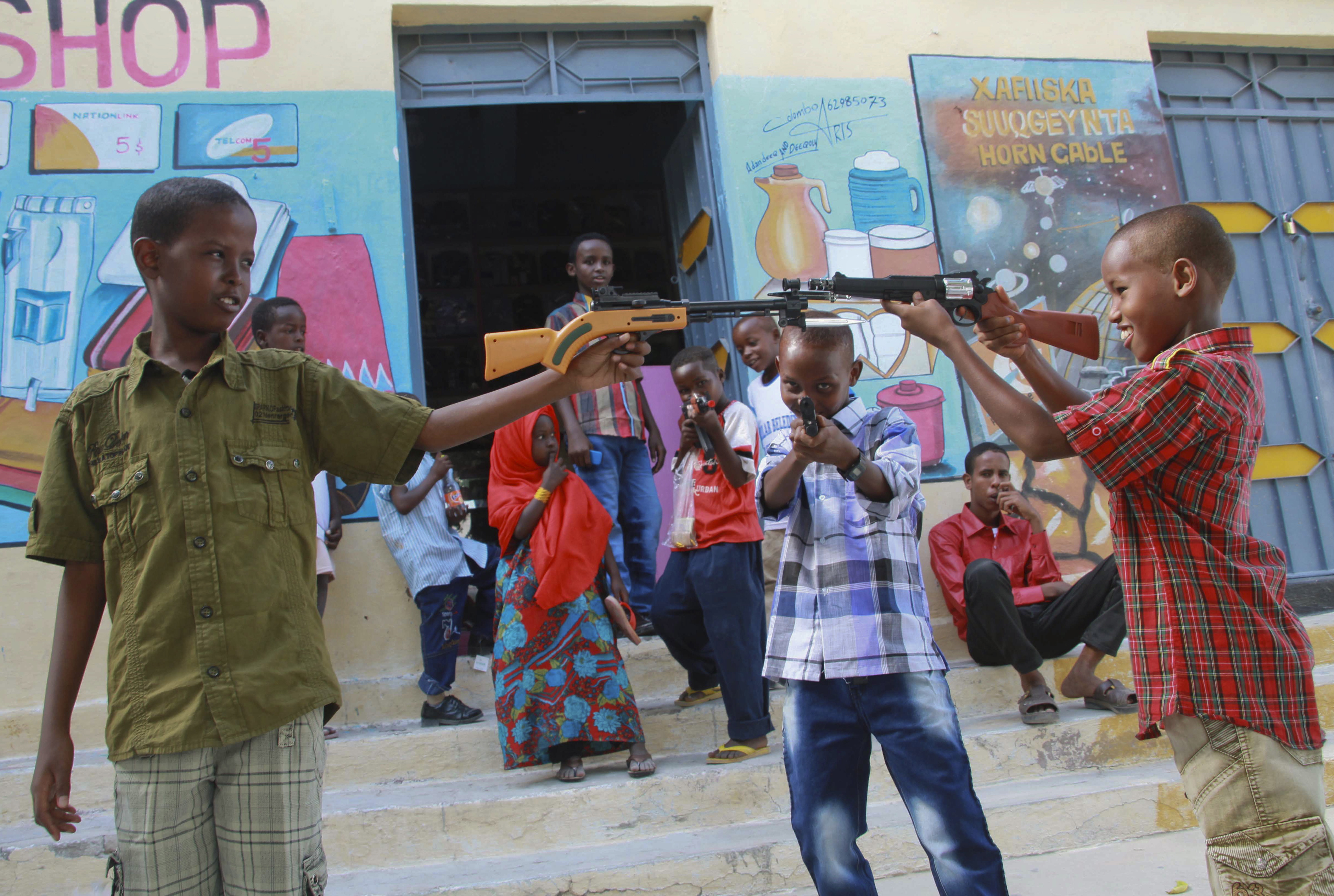 Somali children play with toy guns on the street as worshippers attend the prayer ceremony at the Isbaheysi Mosque in Mogadishu, Somalia, 19 August 2012, to celebrate Muslim holiday Eid al-Fitr which marks the end of the Muslim fasting month of Ramadan.