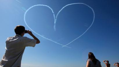 "People look at a heart created by smoke from the L-39 jets of the ""Russ"" aerobatic team"