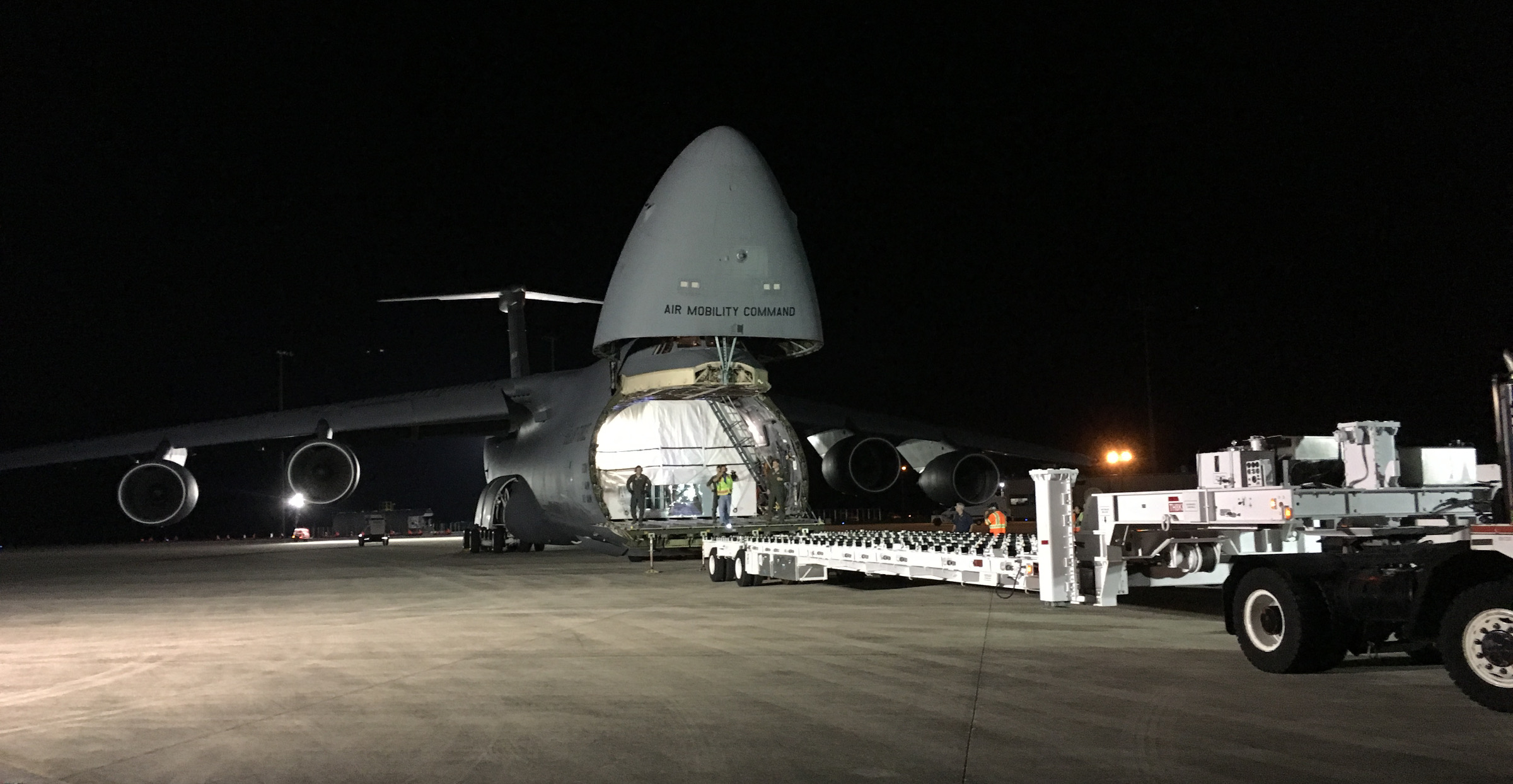 The special flatbed truck has to be lined up perfectly with the front cargo bay of the C-5.