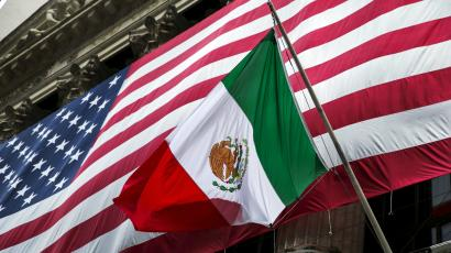 The flag of Mexico in front of a large U.S. flag in front of the New York Stock Exchange