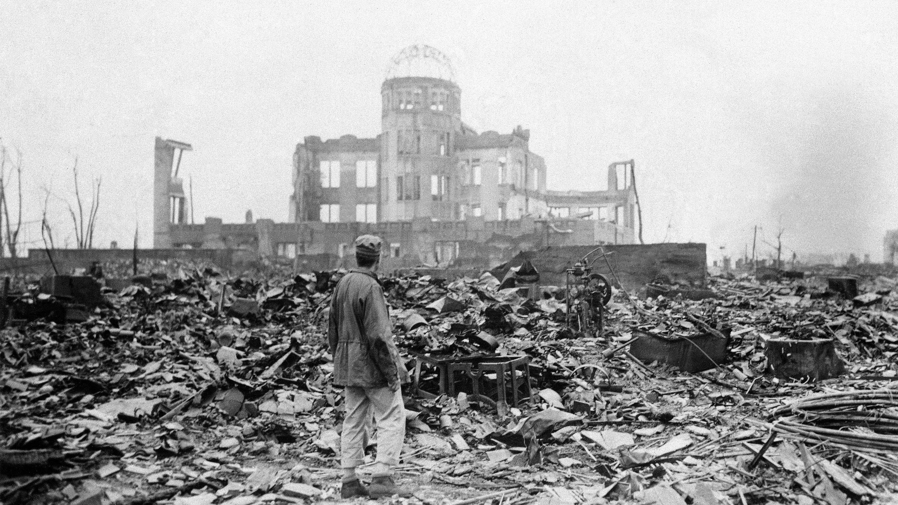 FILE - In this Sept. 8, 1945 file photo, an allied correspondent stands in the rubble in front of the shell of a building that once was a movie theater in Hiroshima, Japan, a month after the first atomic bomb ever used in warfare was dropped by the U.S. on Aug. 6, 1945. A contentious debate over nuclear power in Japan is also bringing another question out of the shadows: Should Japan keep open the possibility of making nuclear weapons _ even if only as an option? It may seem surprising in the only country ever devastated by atomic bombs, particularly as it marks the 67th anniversary of the bombings of Hiroshima on Aug. 6, 2012, and Nagasaki three days later. The Japanese government officially renounces nuclear weapons, and the vast majority of citizens oppose them. The damaged building standing in the background is the Hiroshima Prefectural Industrial Promotion Hall, currently preserved as the Atomic Bomb Dome.