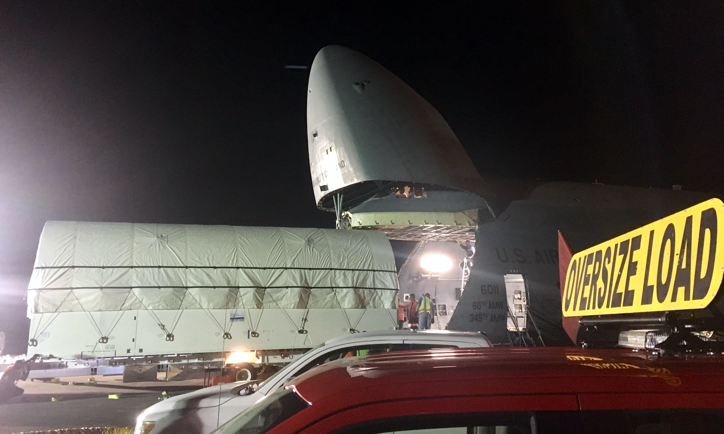 The satellite is completely out of the C-5 as its convoy prepares to depart.