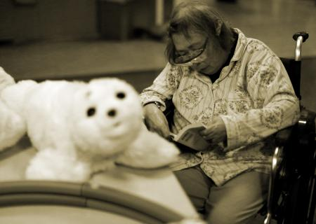 A resident reads a book during a session Paro at Shin-tomi nursing home in Tokyo, Japan.