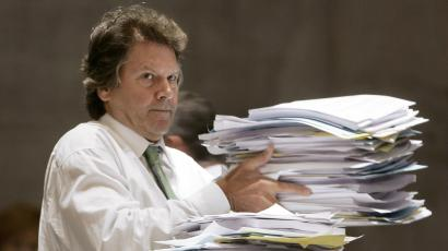 A man with huge stacks of papers