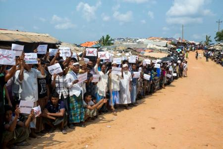 Rohingya refugees holding placards, await the arrival of a U.N. Security Council team in Bangladesh, on April 29, 2018.