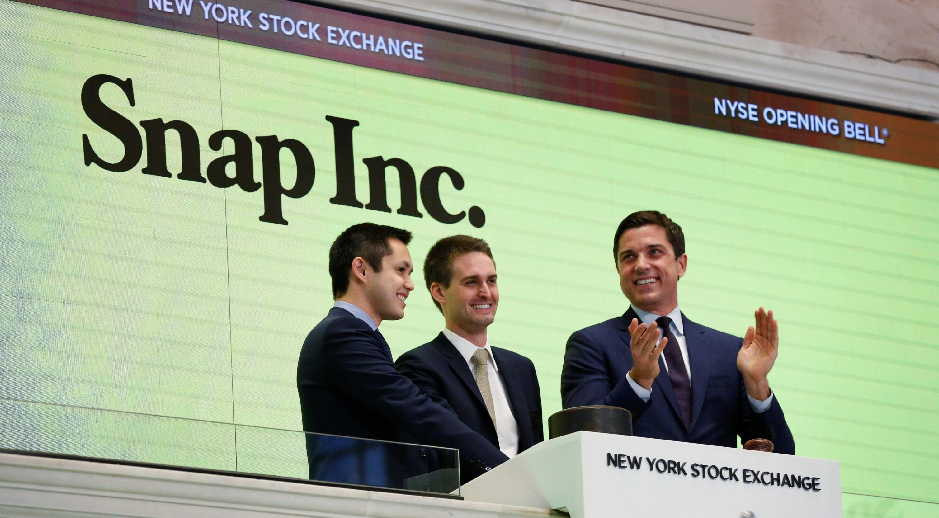 Snap cofounders Evan Spiegel (C) and Bobby Murphy ring the opening bell of the New York Stock Exchange (NYSE) with NYSE Group President Thomas Farley shortly before the company's IPO in New York, U.S., March 2, 2017. REUTERS/Lucas Jackson TPX IMAGES OF THE DAY - RC15379A9A10