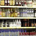 A young man stands in front of a shelve with hard liquor at a beverage market.