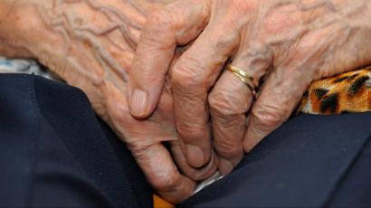 An old person clasping their hands