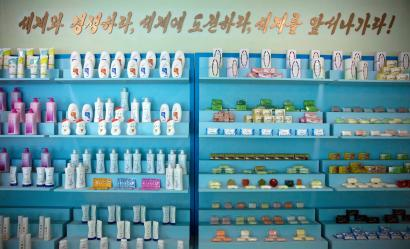 """Inside the Pyongyang Cosmetics Factory. The slogan reads: """"Compete with the world, challenge the world, go lead the world!"""""""