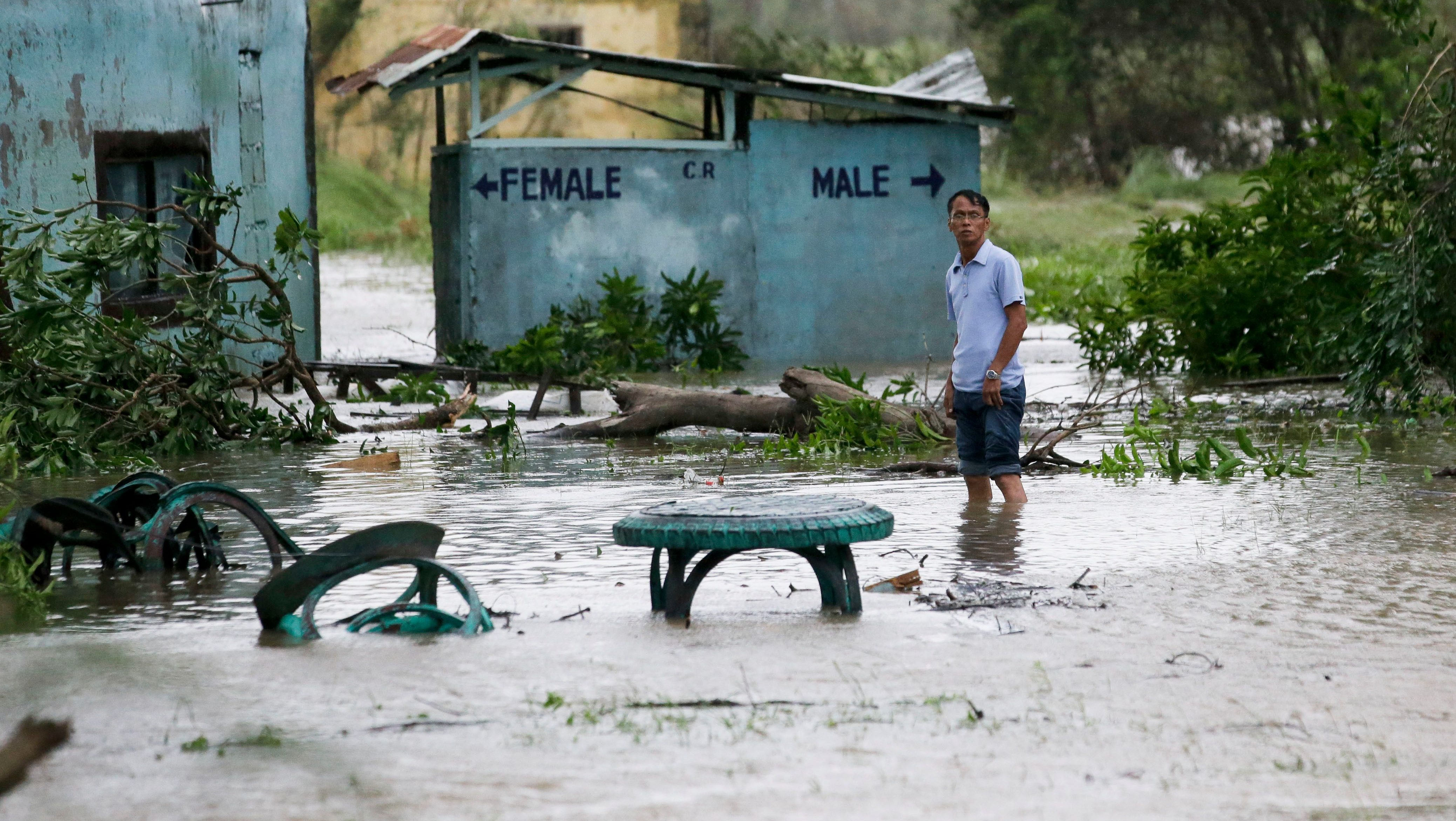 A resident wades along a flooded area as Typhoon Mangkhut barreled across Tuguegarao city in Cagayan province, northeastern Philippines on Saturday, Sept. 15, 2018. The typhoon slammed into the Philippines northeastern coast early Saturday, it's ferocious winds and blinding rain ripping off tin roof sheets and knocking out power, and plowed through the agricultural region at the start of the onslaught.