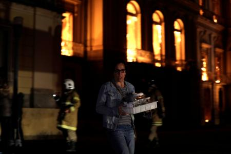 A worker rescues items during a fire at the National Museum of Brazil in Rio de Janeiro, Brazil September 2, 2018. - RC1AC83B67C0