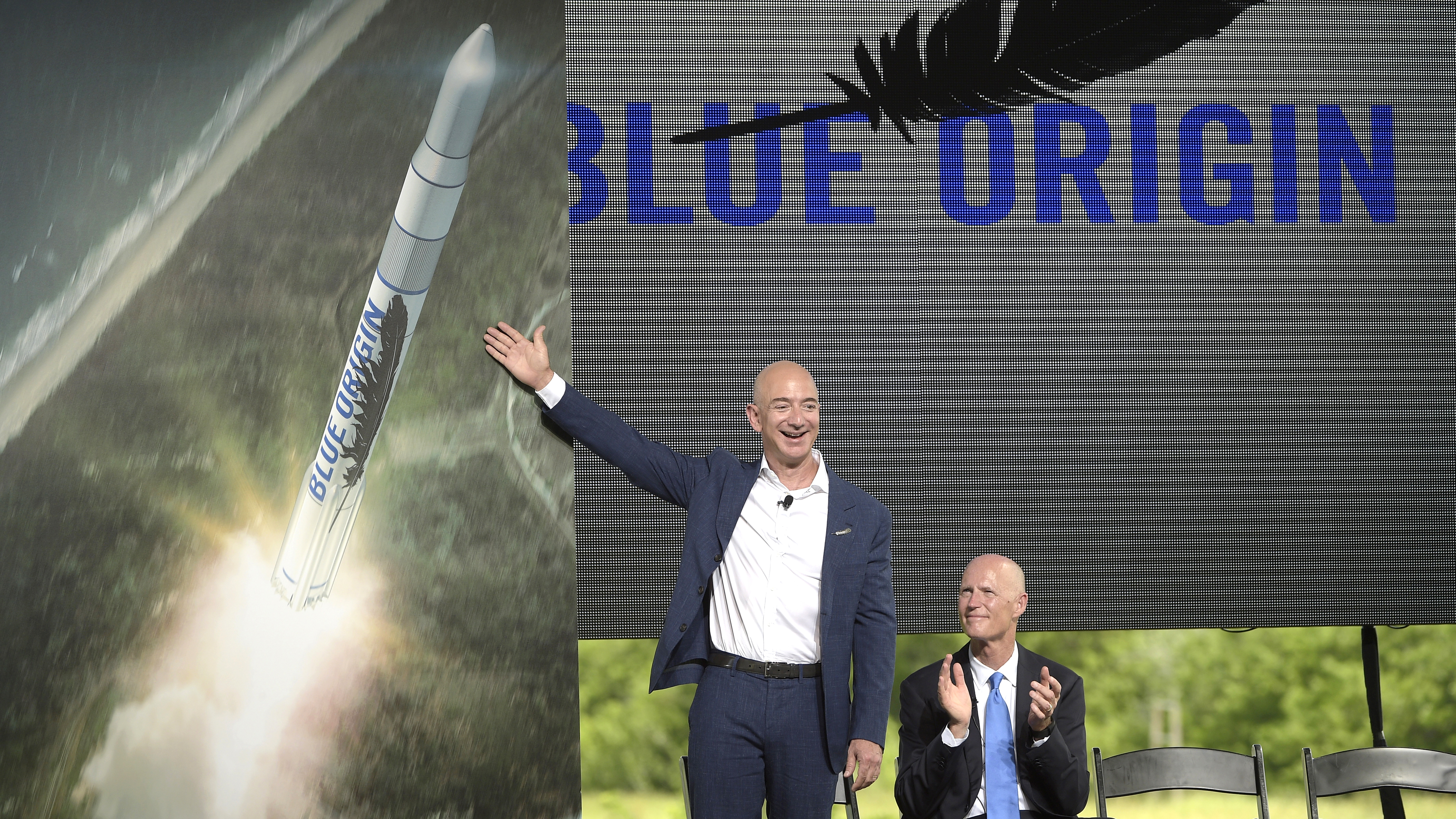 Amazon CEO Jeff Bezos, left, unveils the new Blue Origin rocket, as Florida Gov. Rick Scott, right, applauds during a news conference at the Cape Canaveral Air Force Station in Cape Canaveral, Fla., Tuesday, Sept. 15, 2015. Bezos announced a $200 million investment to build the rockets and capsules in the state and launch them using the historic Launch Complex 36.