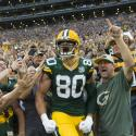 A Green Bay Packers players celebrating a touchdown with fans.