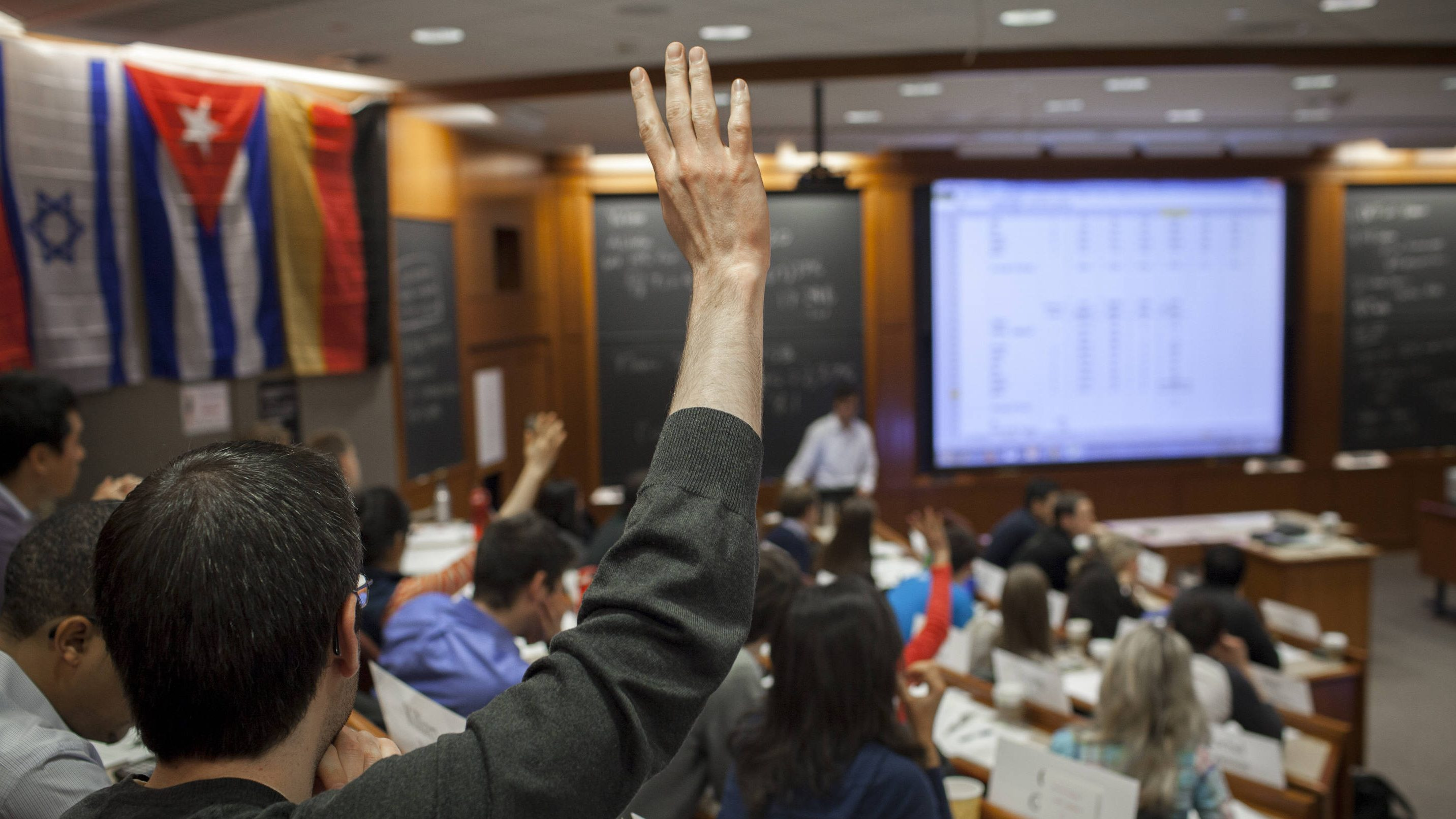 An HBS student raises his hand