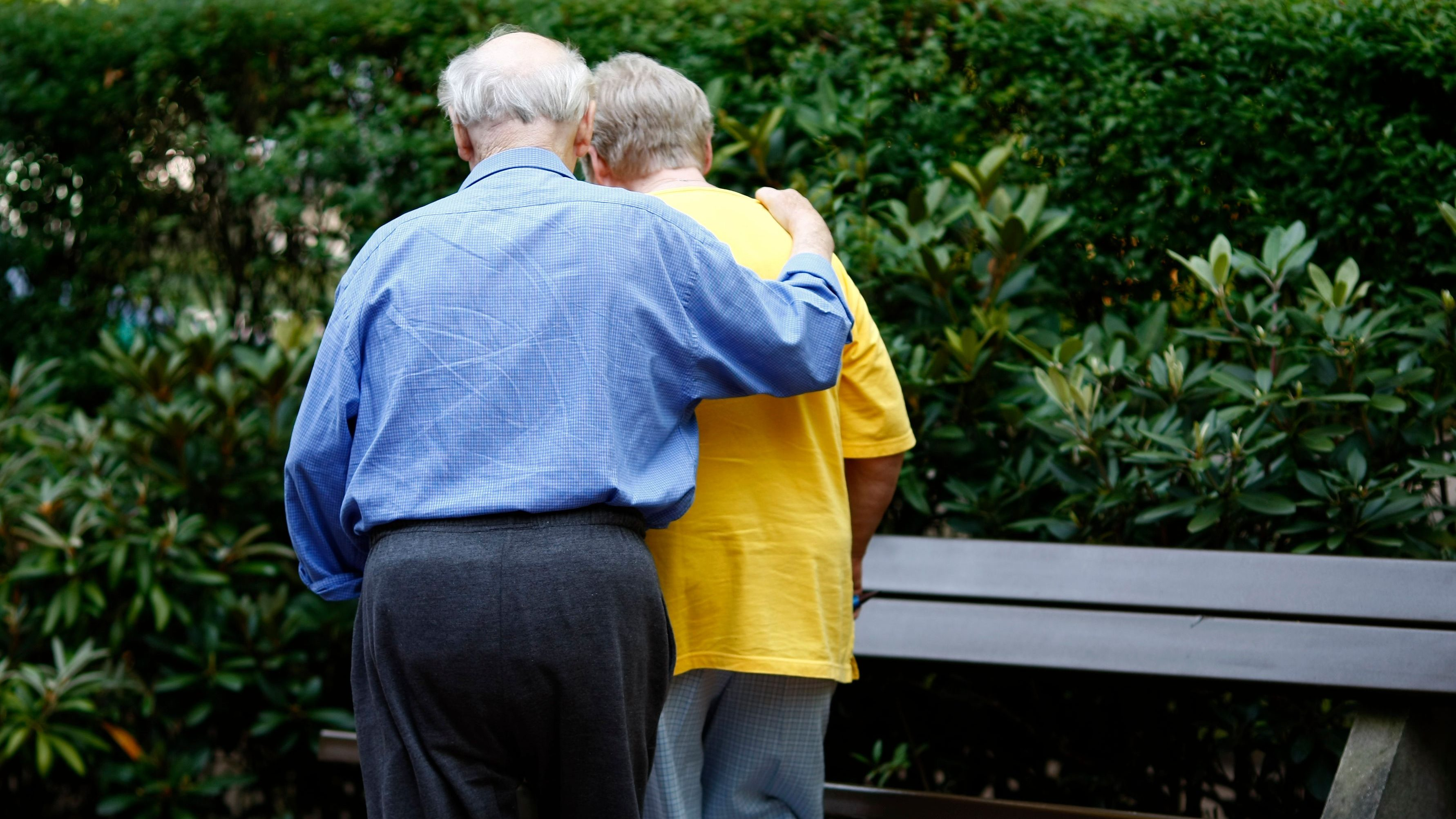 The back of an elderly couple walking.