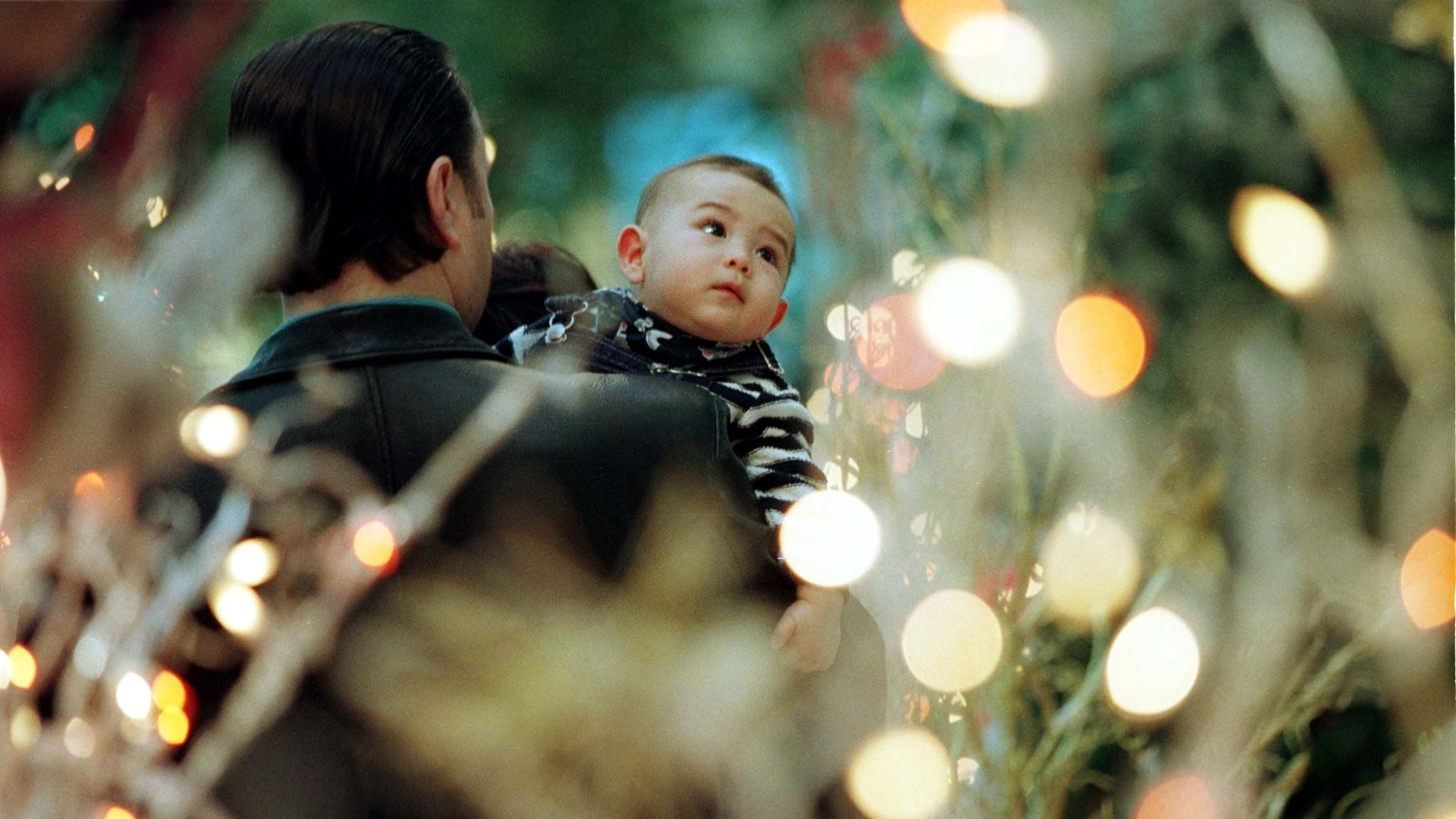 A baby looks at Christmas tree lights.