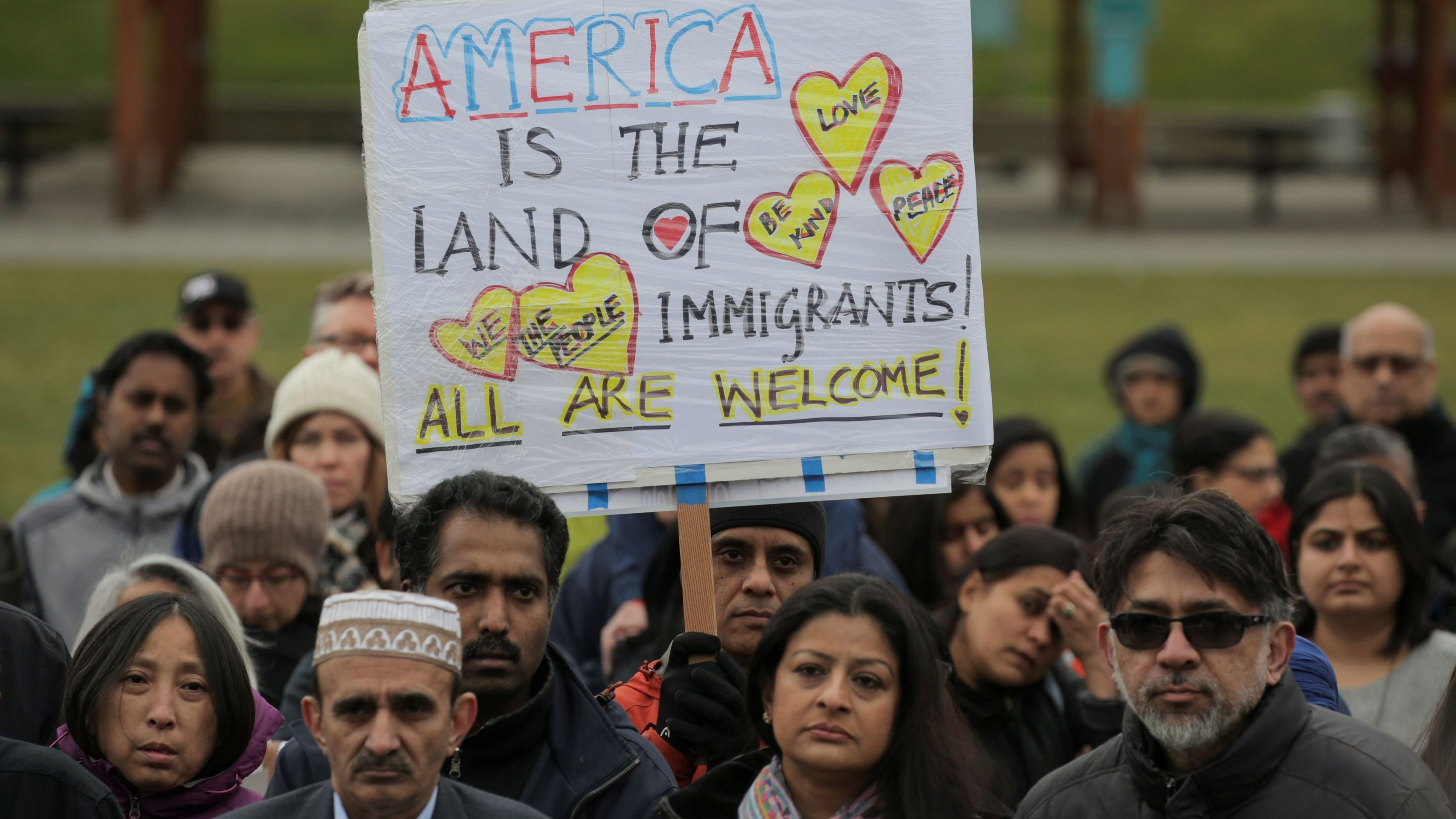 People listen during a vigil in honor of Srinivas Kuchibhotla, an immigrant from India who was recently shot and killed in Kansas, at Crossroads Park in Bellevue, Washington
