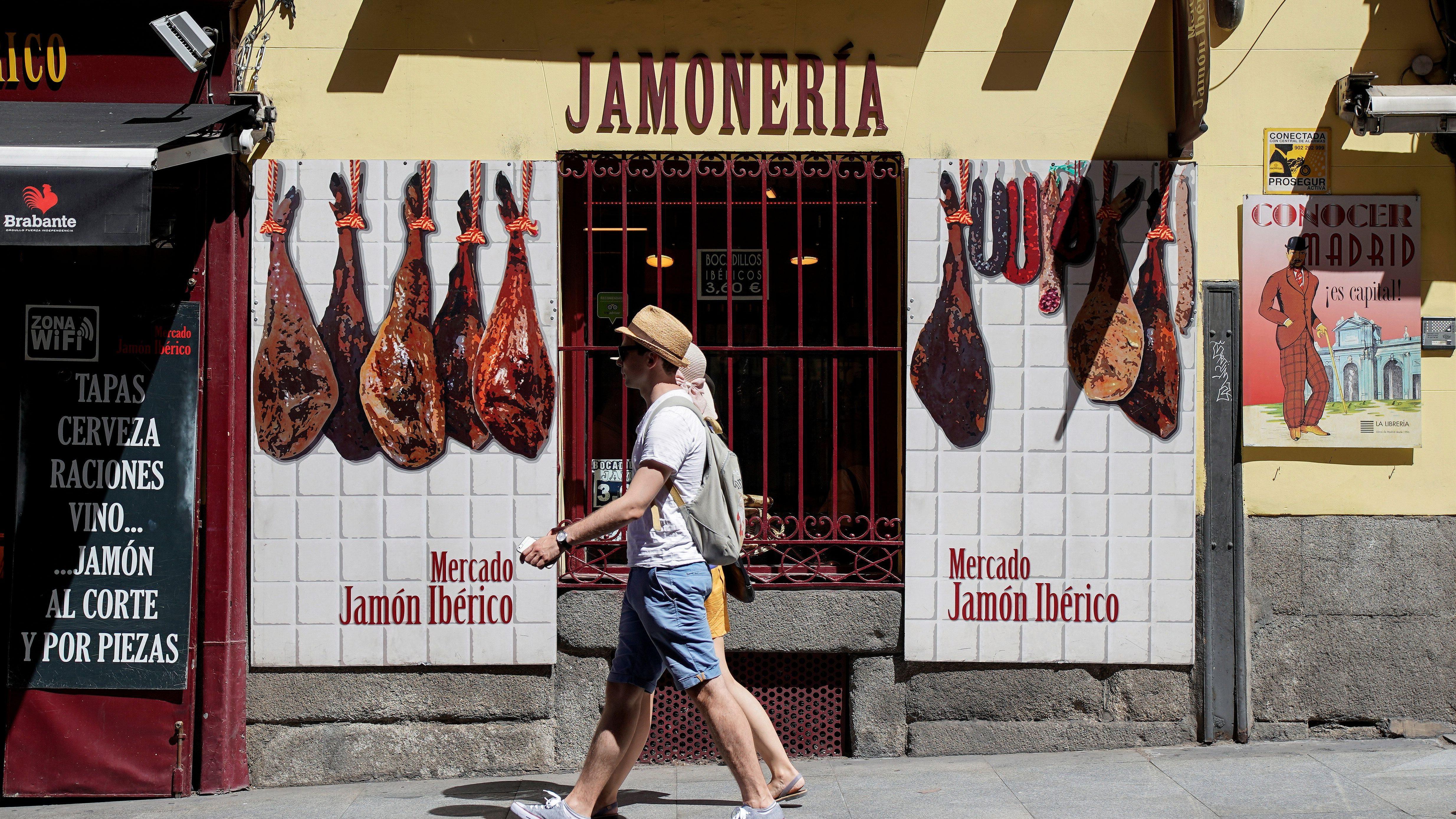 Tourists walk past a Spanish Iberico ham shop in Madrid