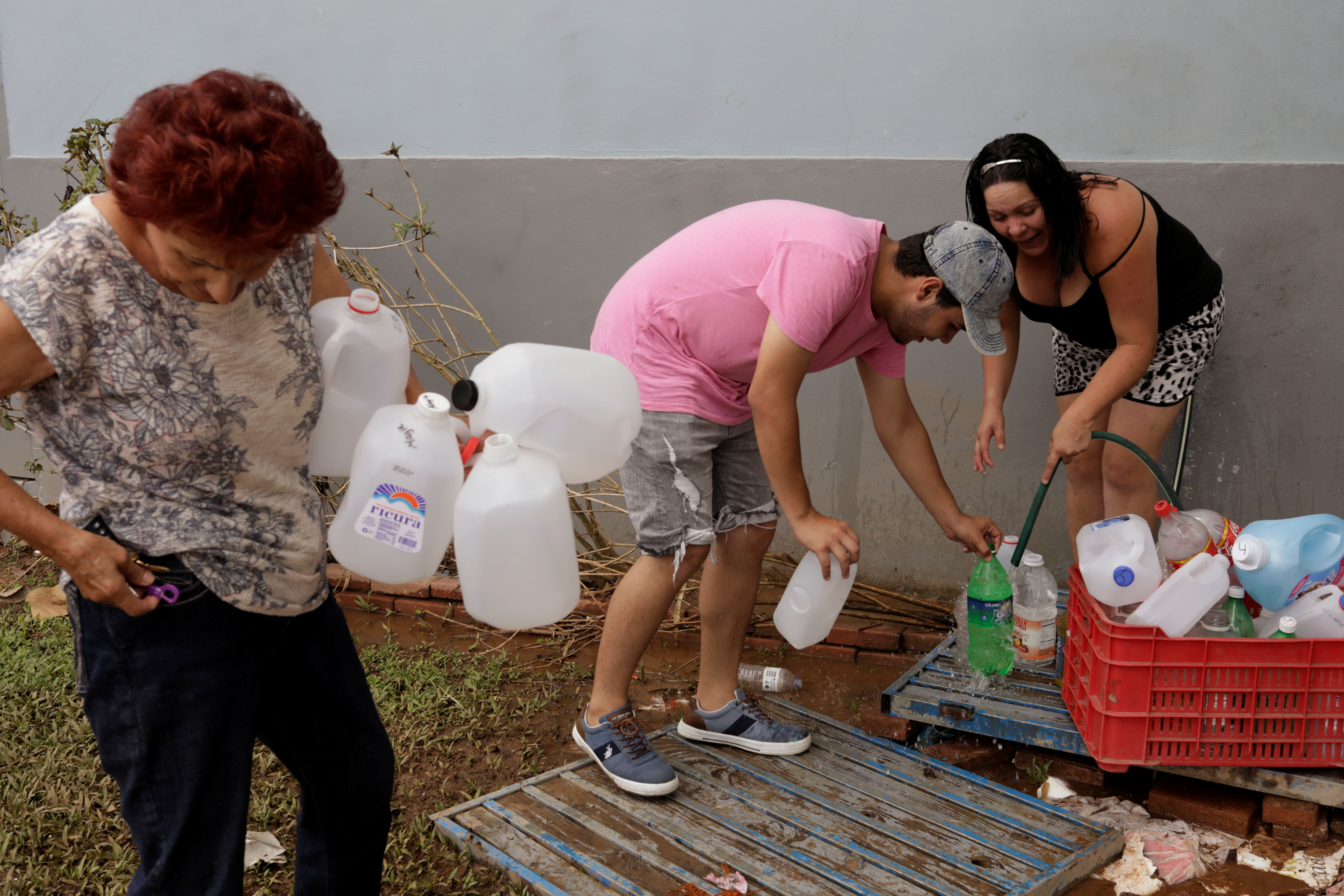 Residents use a water faucet on the side of a building to fill water jugs due to lack of water service following Hurricane Maria