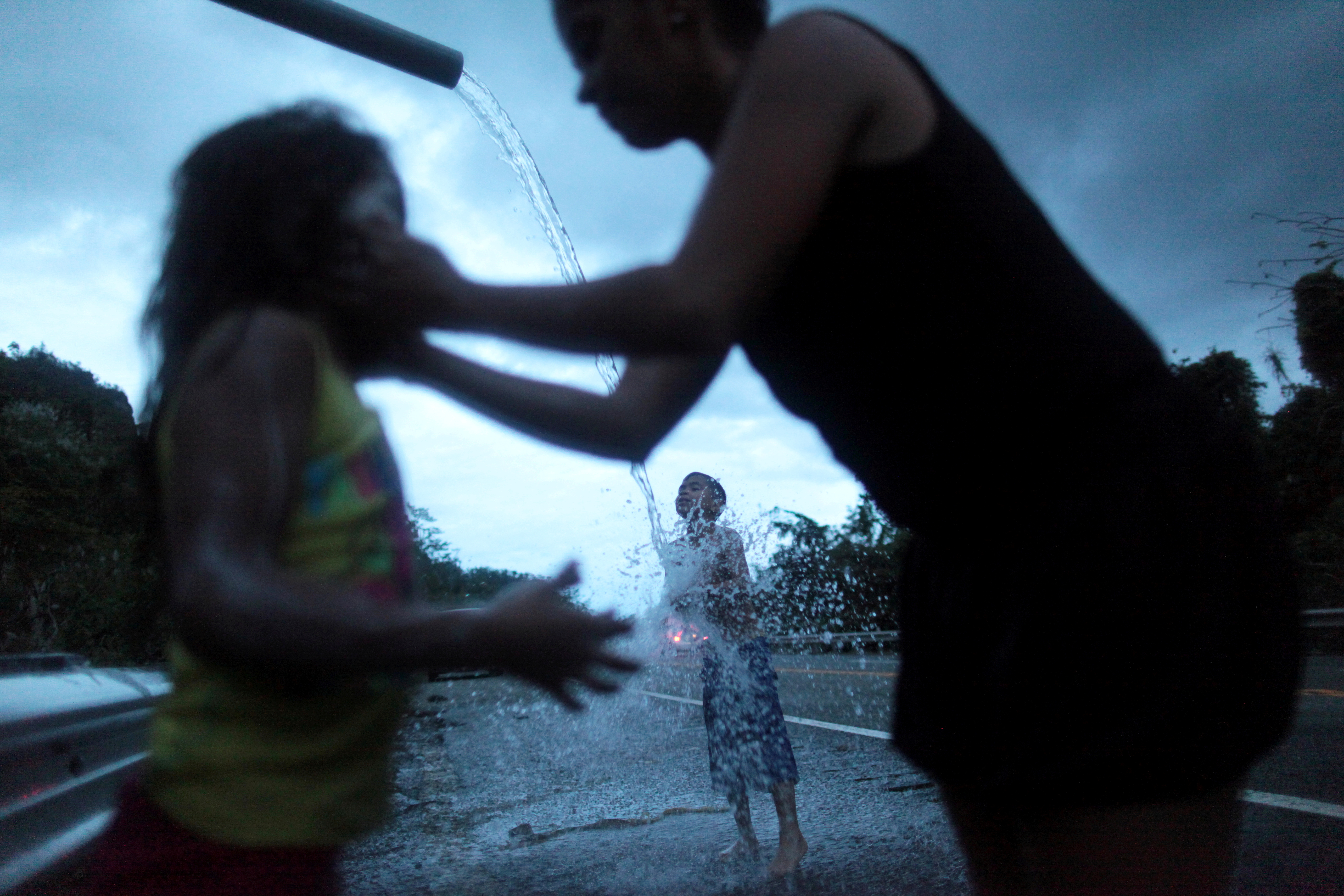 A family bathe with mountain spring water after hurricane Maria hit Puerto Rico
