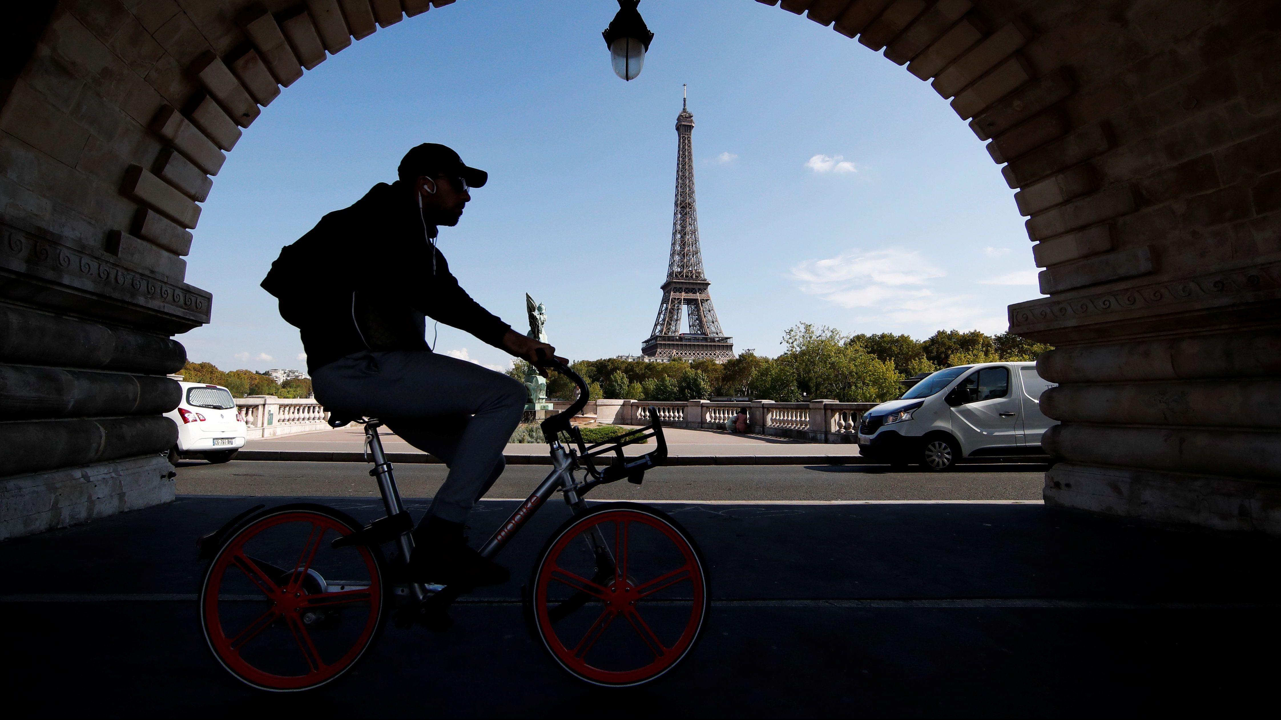 A man rides a bike-sharing service mobike bicycle at the Pont de Bir-Hakeim birdge near the Eiffel Tower in Pairs