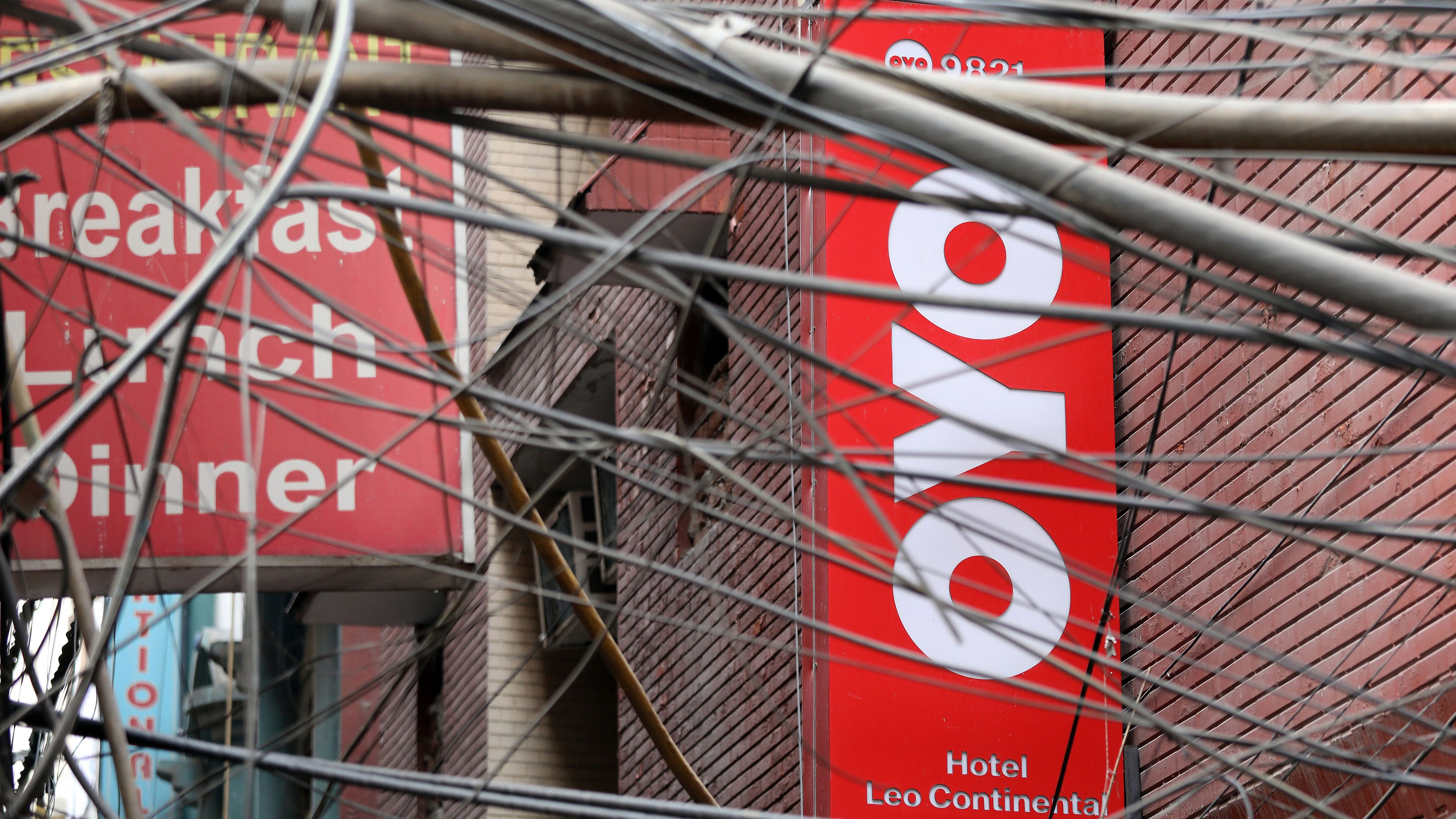 The logo of OYO, India's largest and fastest-growing hotel chain, installed on a hotel building is seen through wires in an alley in New Delhi