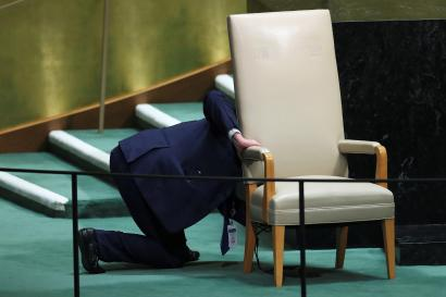 A worker prepares to remove a chair reserved for heads of state from the stage during the 73rd session of the United Nations General Assembly in New York, U.S., September 27, 2018. REUTERS/Carlo Allegri - RC1E36432030