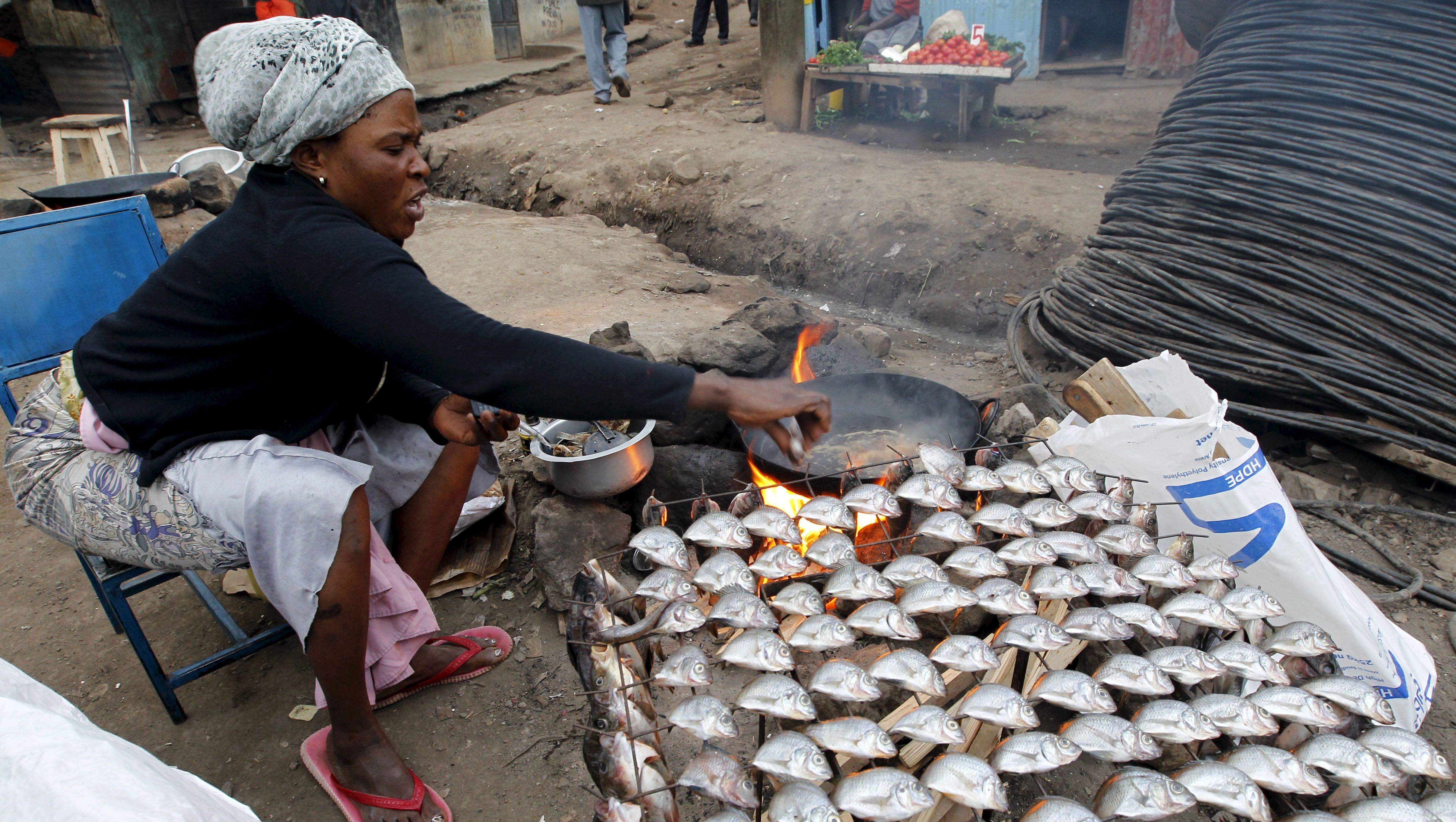 A woman fries fish for sale at her open stall within Mathare valley slums in Kenya's capital Nairobi, July 9, 2015.