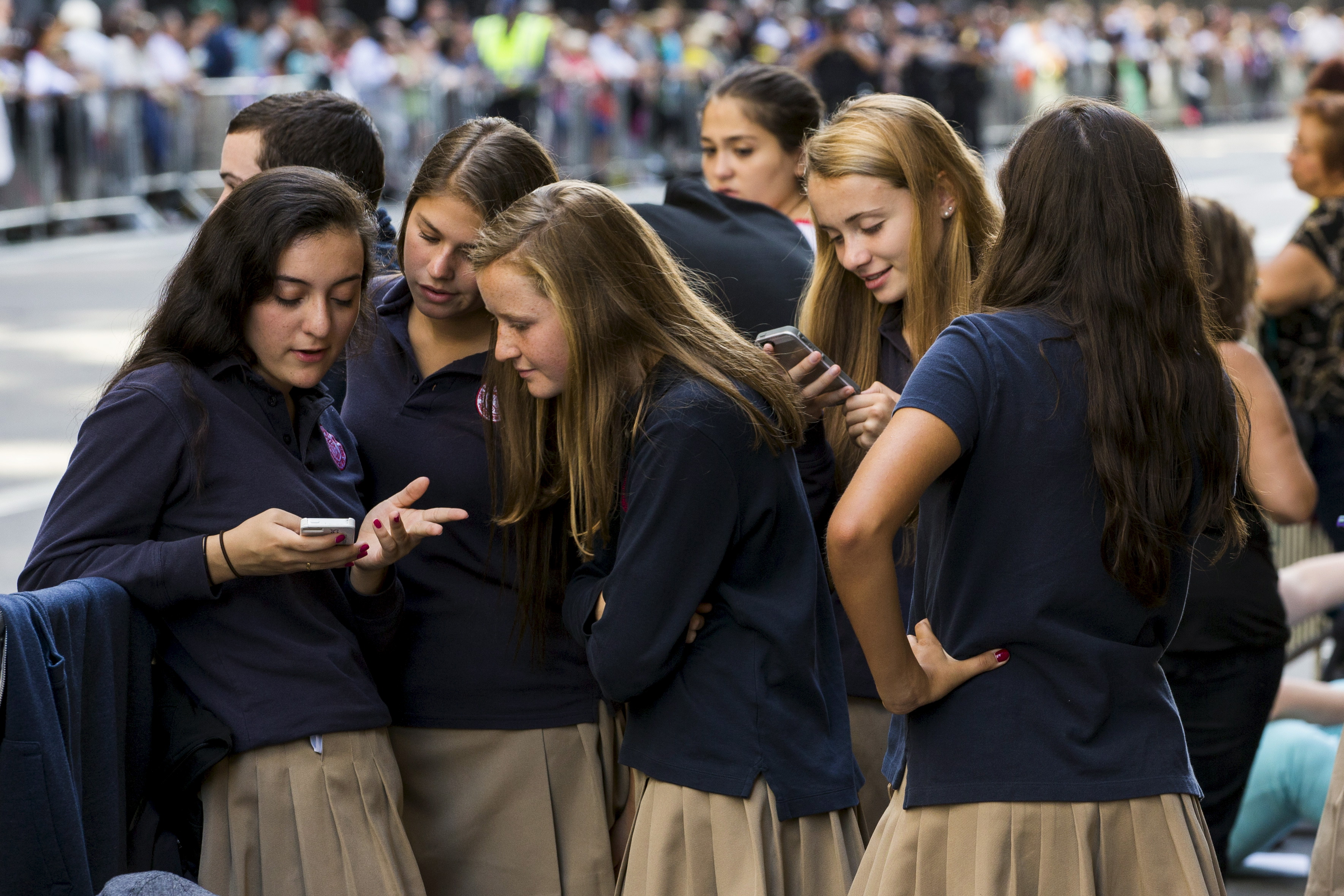 A group of Catholic school girls look at their phones as they wait on the route that Pope Francis will take later in the day near St. Patrick's Cathedral in New York September 24, 2015. REUTERS/Lucas Jackson - GF10000219774