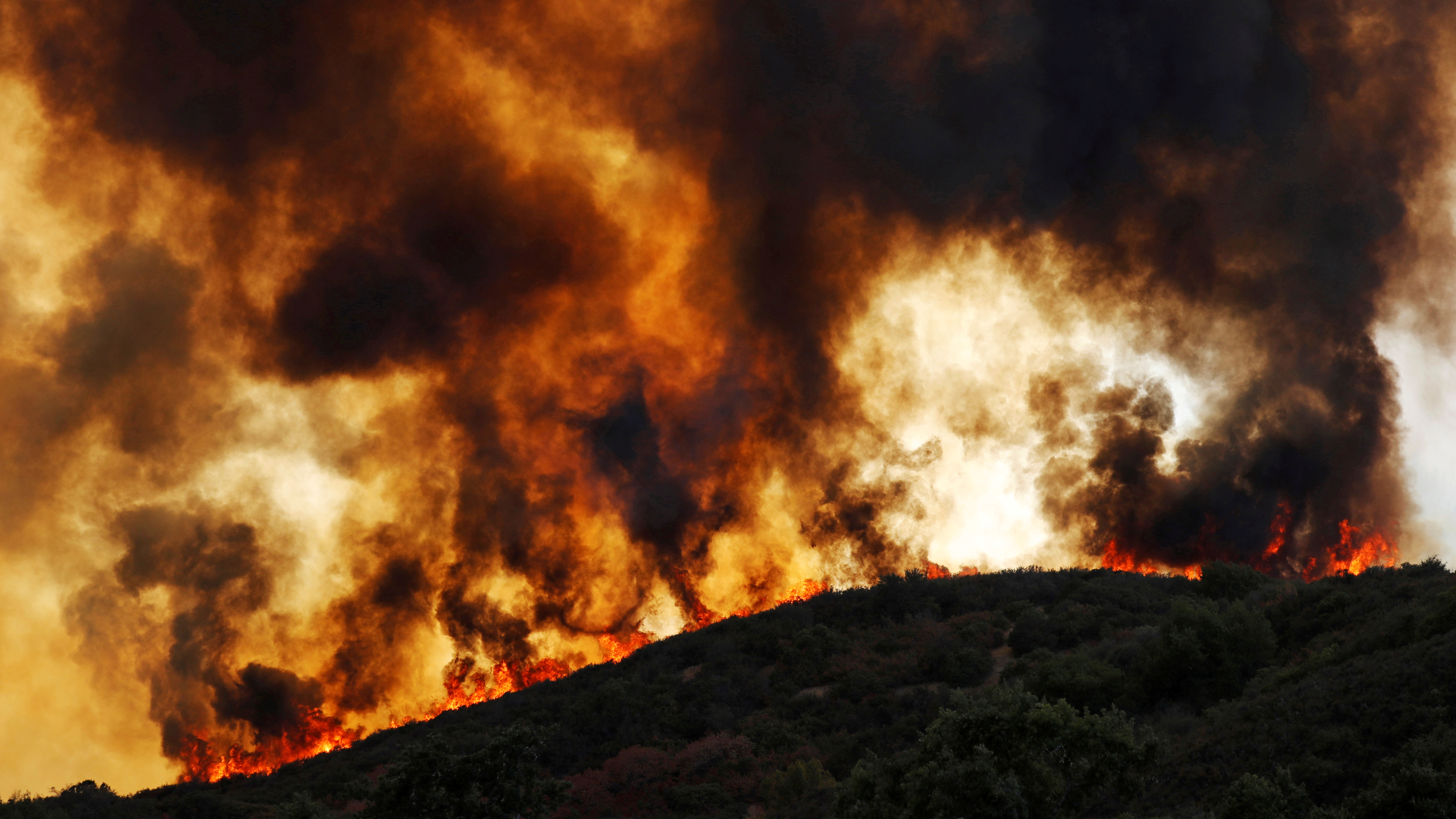 Wind-driven flames roll over a hill towards homes during the River Fire (Mendocino Complex) near Lakeport, California, U.S. August 2, 2018.