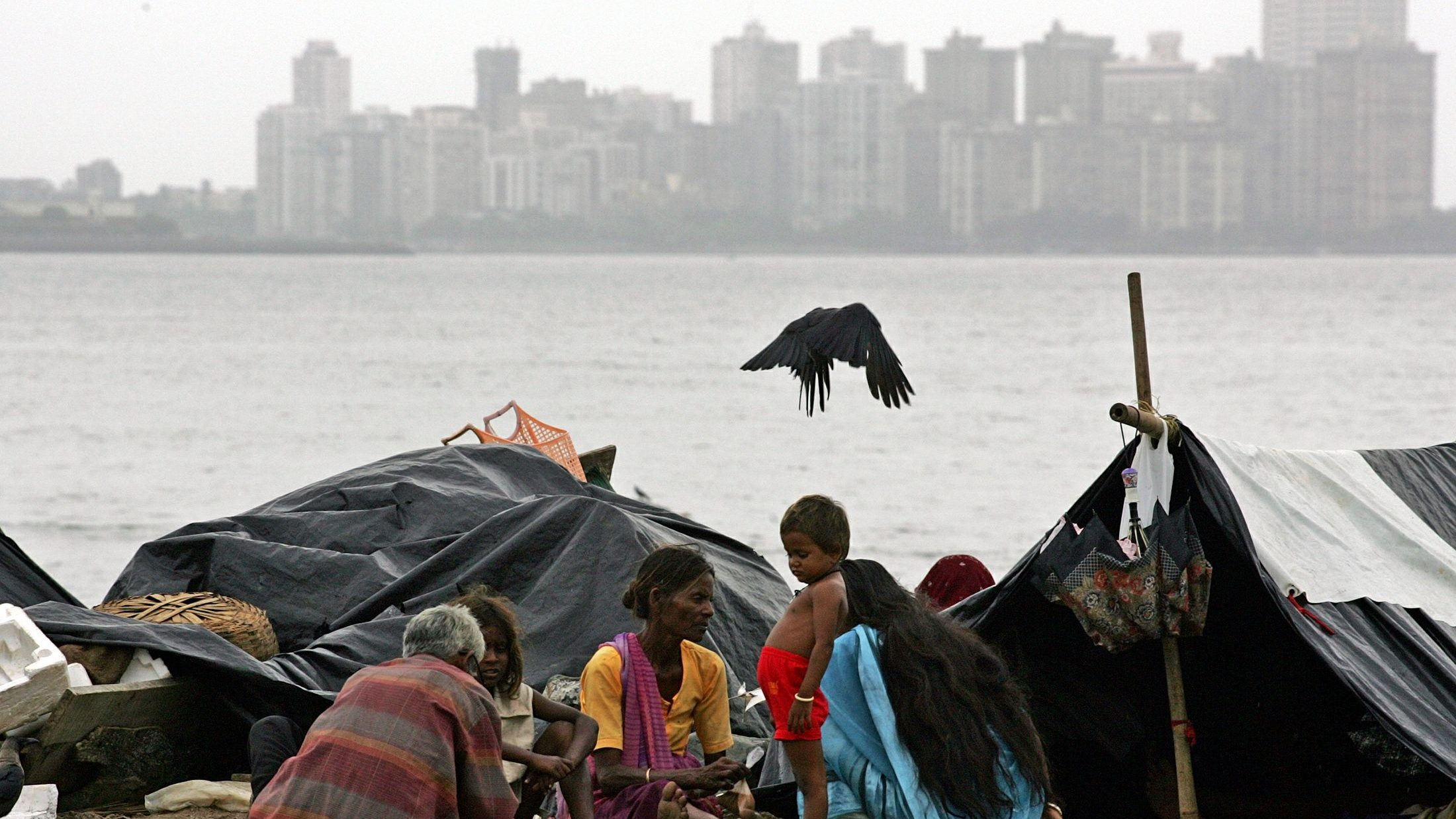 A homeless Indian family sits on a beach in Bombay August 4, 2005. [India's share index rose to its ..
